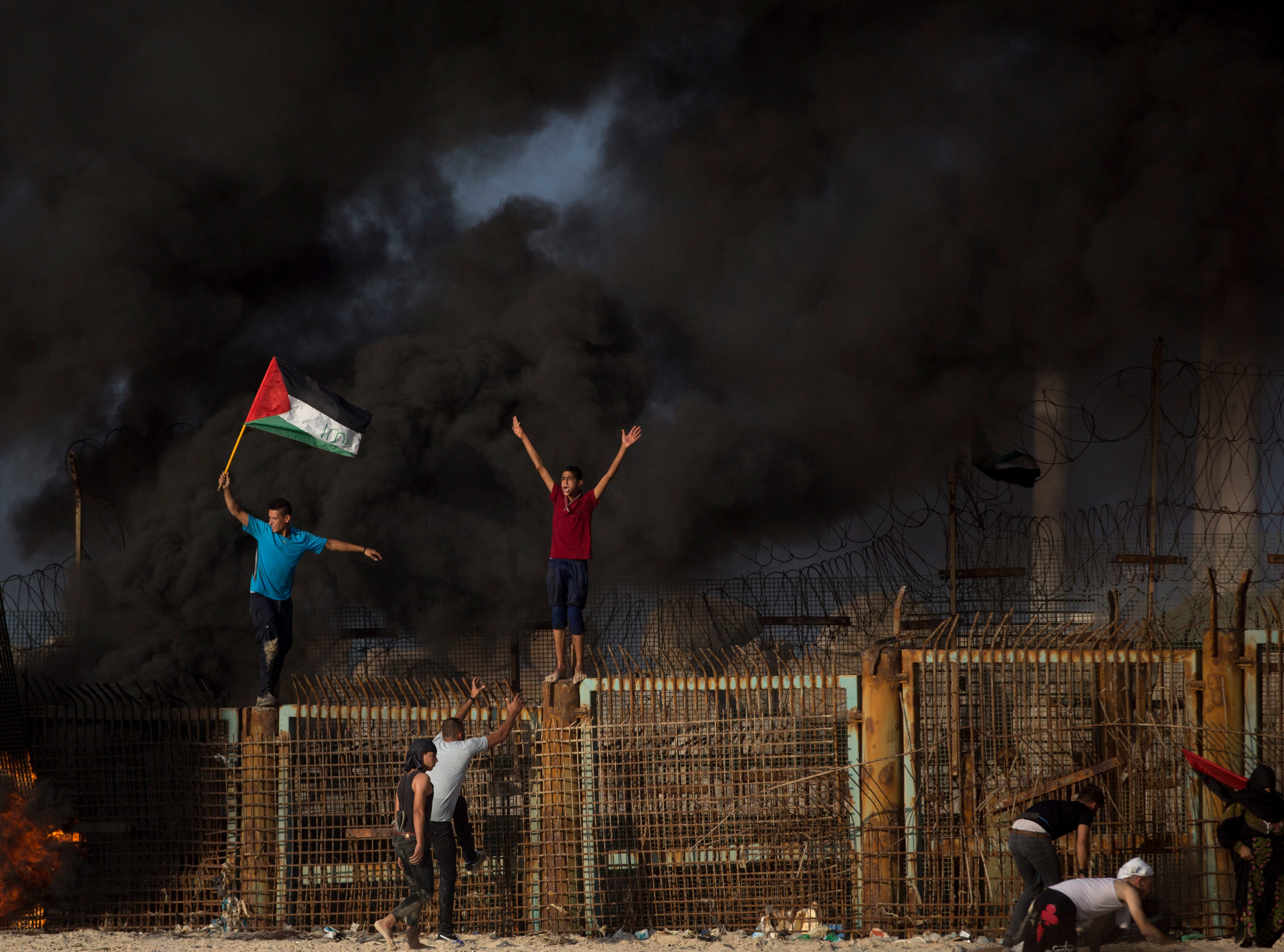 Palestinian protesters climb over the fence at the border with Israel near Beit Lahiya, northern Gaza Strip, Monday, Oct. 15,