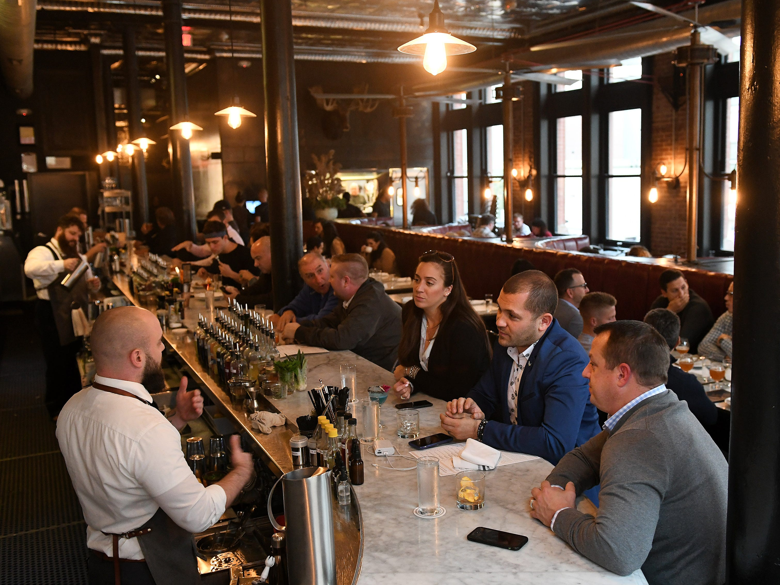 Bar manager Burch, left, talks with, from right, Paul Wolfe of Royal Oak, Emile Chaillot of Chicago and Brittany Siravo of Royal Oak at Wright & Co. in Detroit on Oct 11, 2018.
