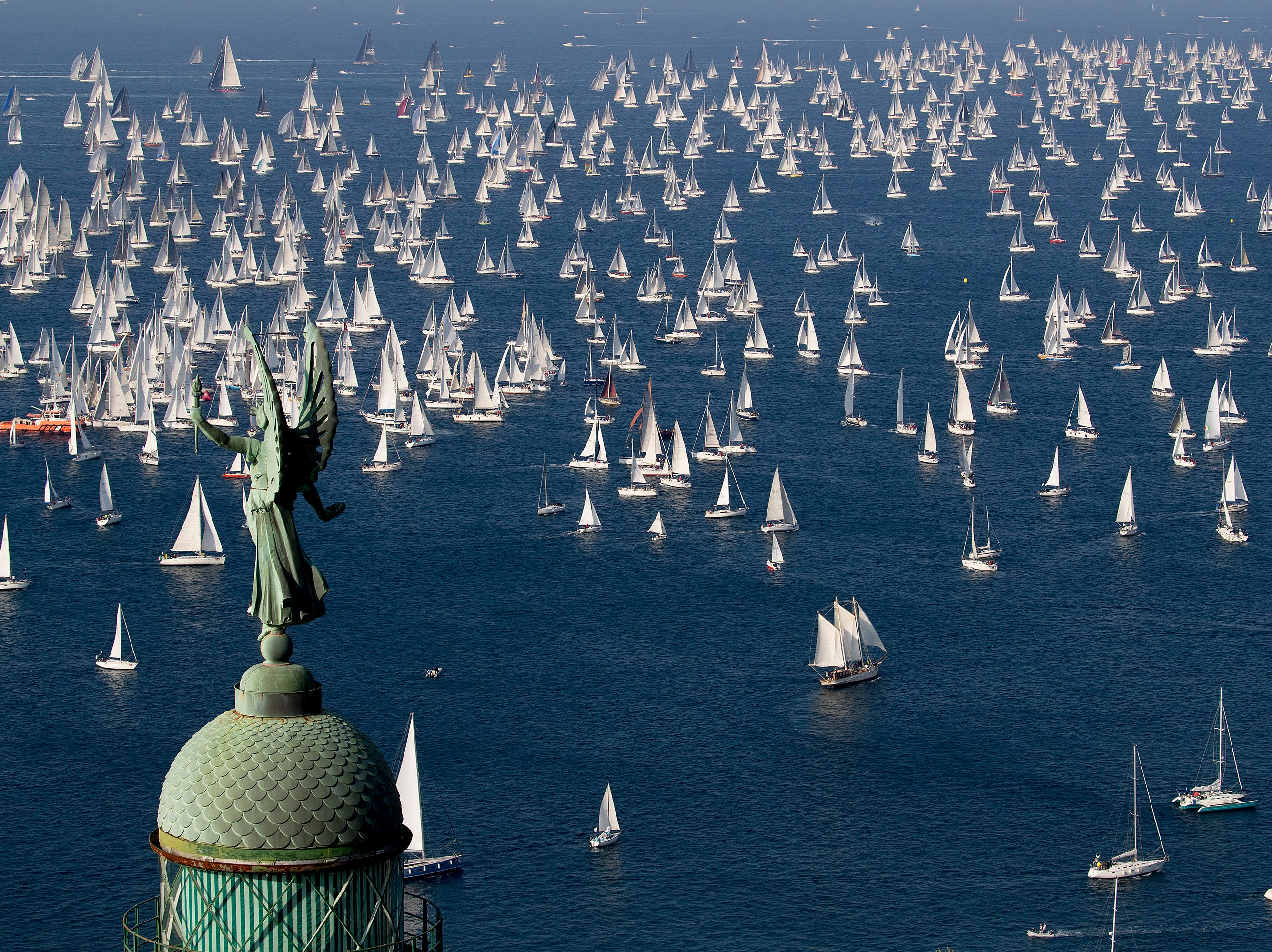 "A view of the sail boats taking part in the 50th edition of the traditional ""Barcolana"" regatta in the gulf of Trieste, north-eastern Italy, Sunday, Oct. 14, 2018. The Barcolana is an annual sailing race in the Gulf of Trieste with hundreds of participants which is described by the organizers as ""everybody's regatta."" In foreground, the ""Victory Lighthouse""."