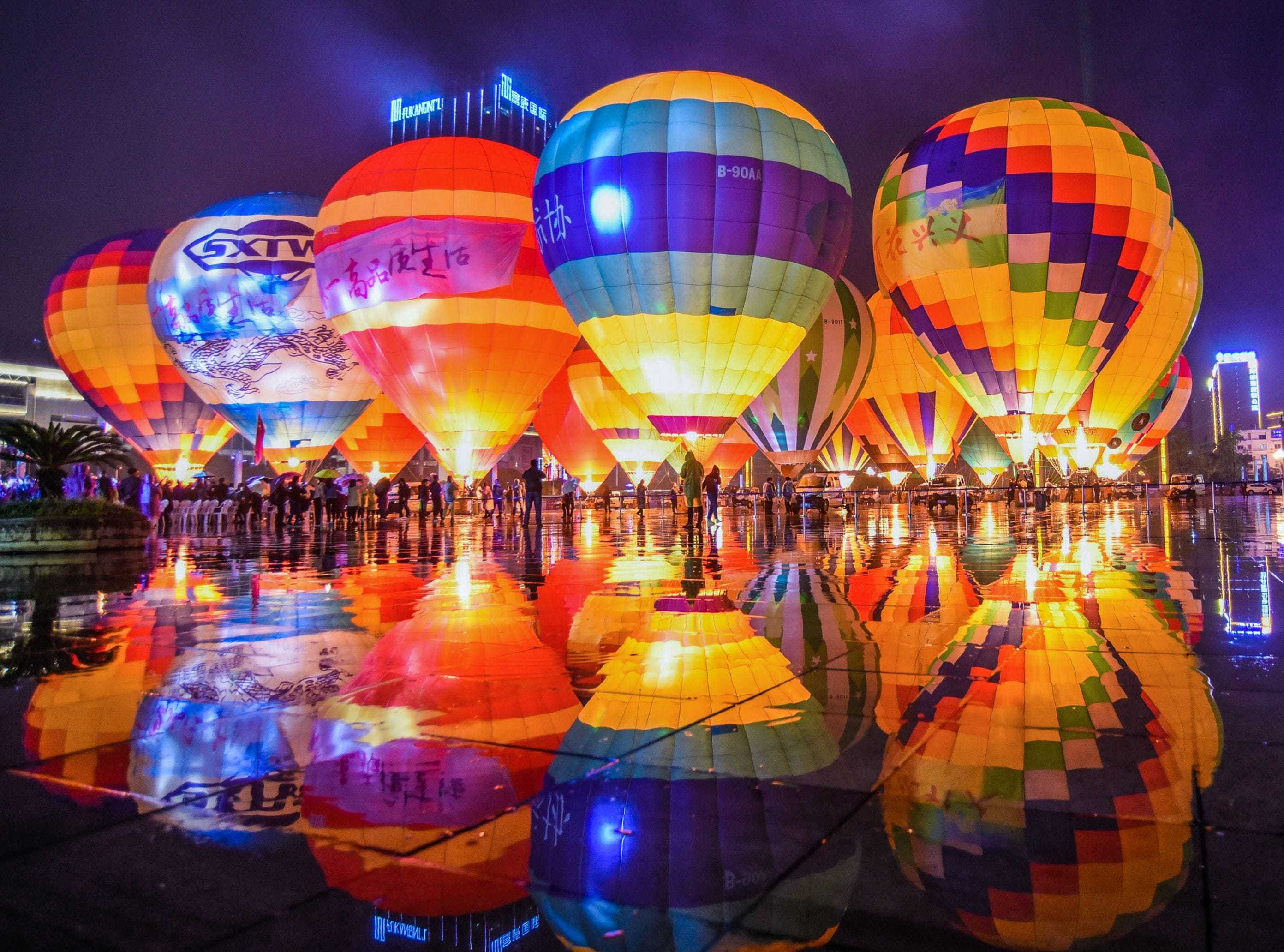 Hot air balloons are displayed on a square Sunday, Oct. 14, 2018, during the 2018 Outdoor Sports Conference in Xingyi in China's southwestern Guizhou province.