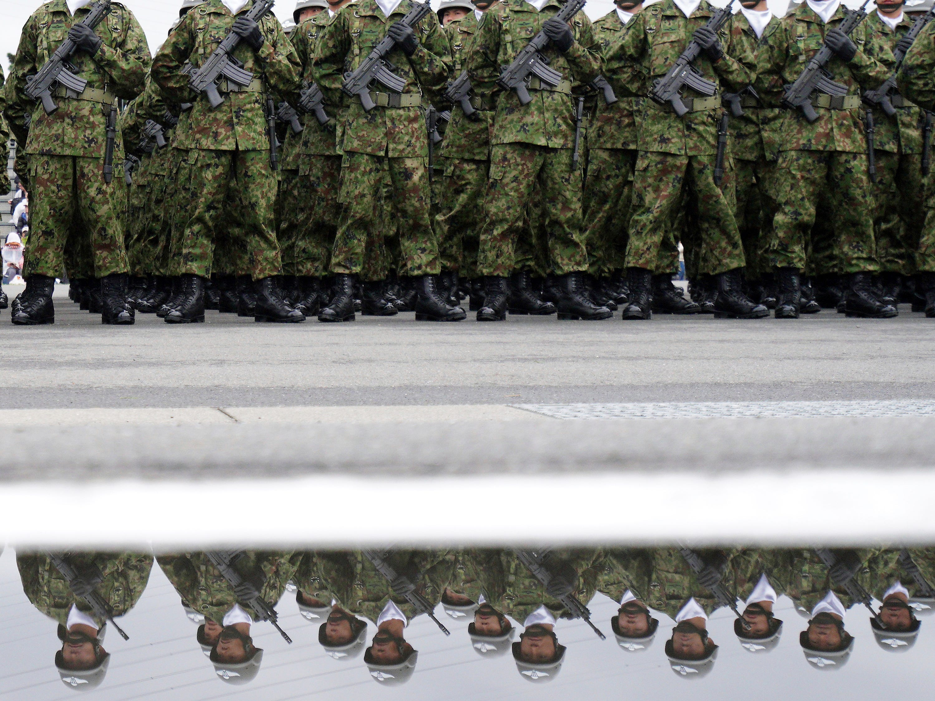 Members of Japan Self-Defense Forces (SDF) stand during the Self-Defense Forces Day at Asaka Base in Asaka, north of Tokyo, Sunday, Oct. 14, 2018. Prime Minister Shinzo Abe renewed his pledge to push for a revision to Japan's war-renouncing constitution at an annual defense review. (AP Photo/Eugene Hoshiko)