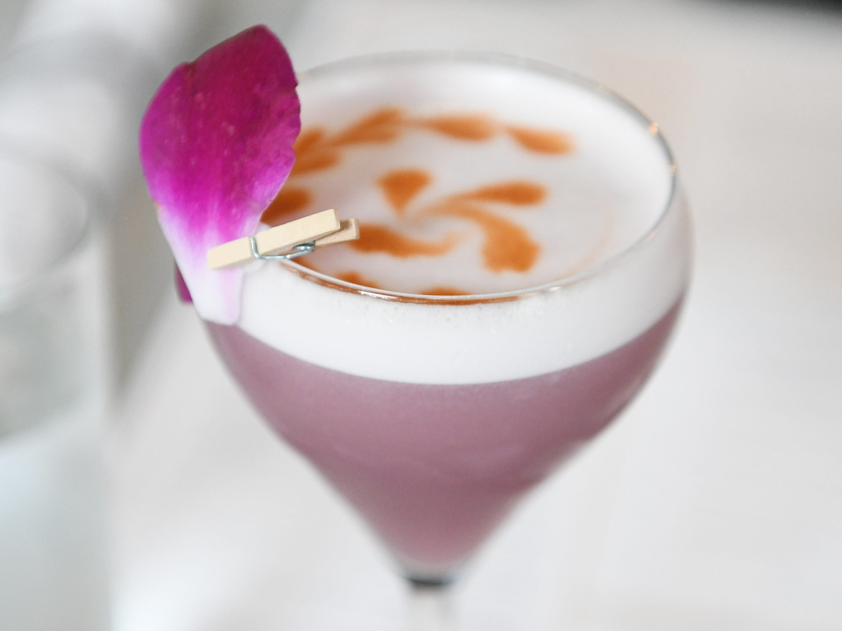 A drink called Still Life made with Citadelle gin, mulled wine reduction, lemon, becherovka, absinthe, egg white and decorated with an orchid.