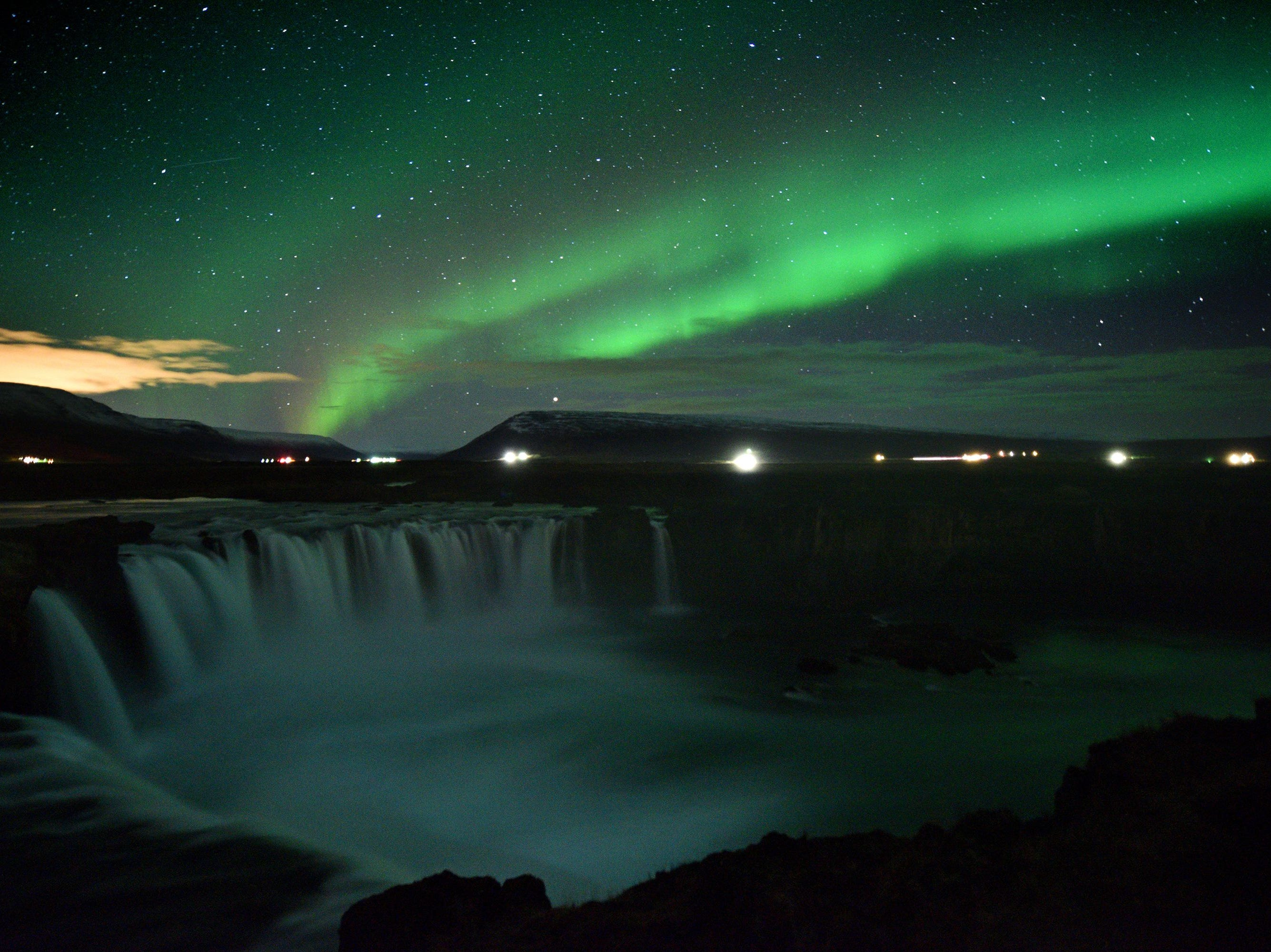 The aurora borealis, also known as Northern Lights, is seen over Godafoss waterfall, in the municipality of Thingeyjarsveit, east of Akureyri, in northern Iceland on October 14, 2018.