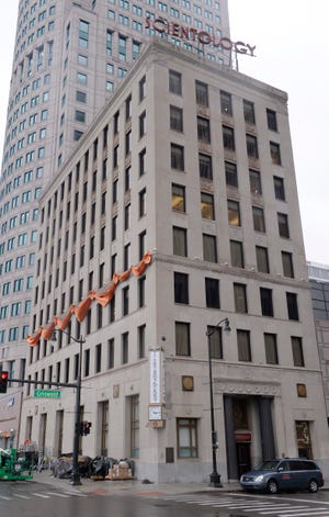 An orange banner is hung for the opening of the new Scientology church on the corners of Griswold and Jefferson in downtown Detroit, Monday.