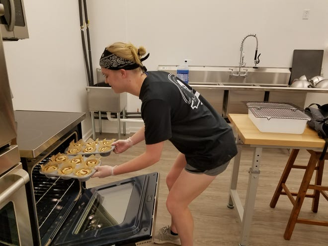 Katelyn Freimiller pops pumpkin cinnamon rolls into the oven in the kitchen of Because Bread Bakery.
