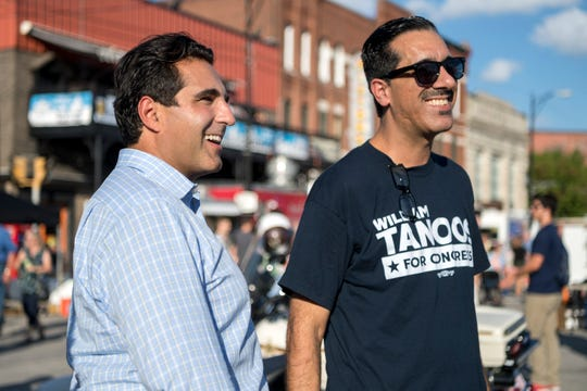 William Tanoos, left, and his uncle TJ Tanoos, right, mingle with West Side Nut Club Fall Festival goers along Franklin Street in Evansville, Ind., Wednesday, Oct. 3, 2018. William is a democratic candidate running against Larry Bucshon in the U.S. House race to represent the 8th Congressional District of Indiana.