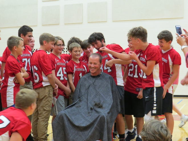 Port Clinton Coach Jared Rhode gets his head shaved by his football team.