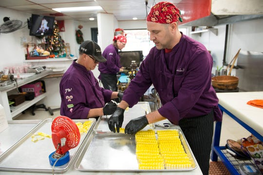 John Buoniconti, front, lays out rows of ribbon candy as they are cut on the production line at the Colorado Candy Company on Monday, October 15, 2018. The Fort Collins company specializes in hard candies and brittles in small batches.