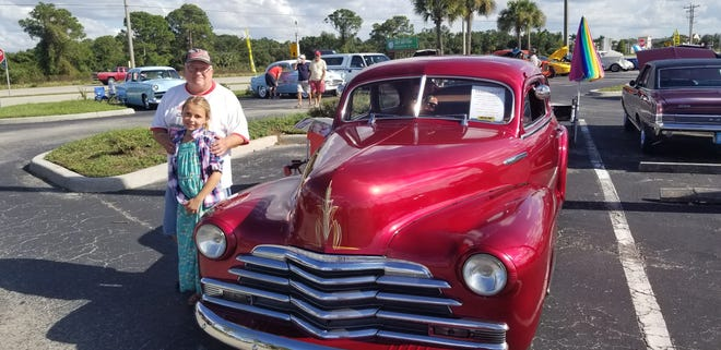 Ray Faulk of Indiana, newly arrived for the winter season, with great-granddaughter Brianna with his 1948 Chevrolet, one of the vehicles on display at the car show at Merchants Crossing in North Fort Myers. Faulk recently drove the vehicle 1,200 miles from Fort Wayne to spend winter with his family in Cape Coral. A zoning change is being made to allow the car show every Monday,.