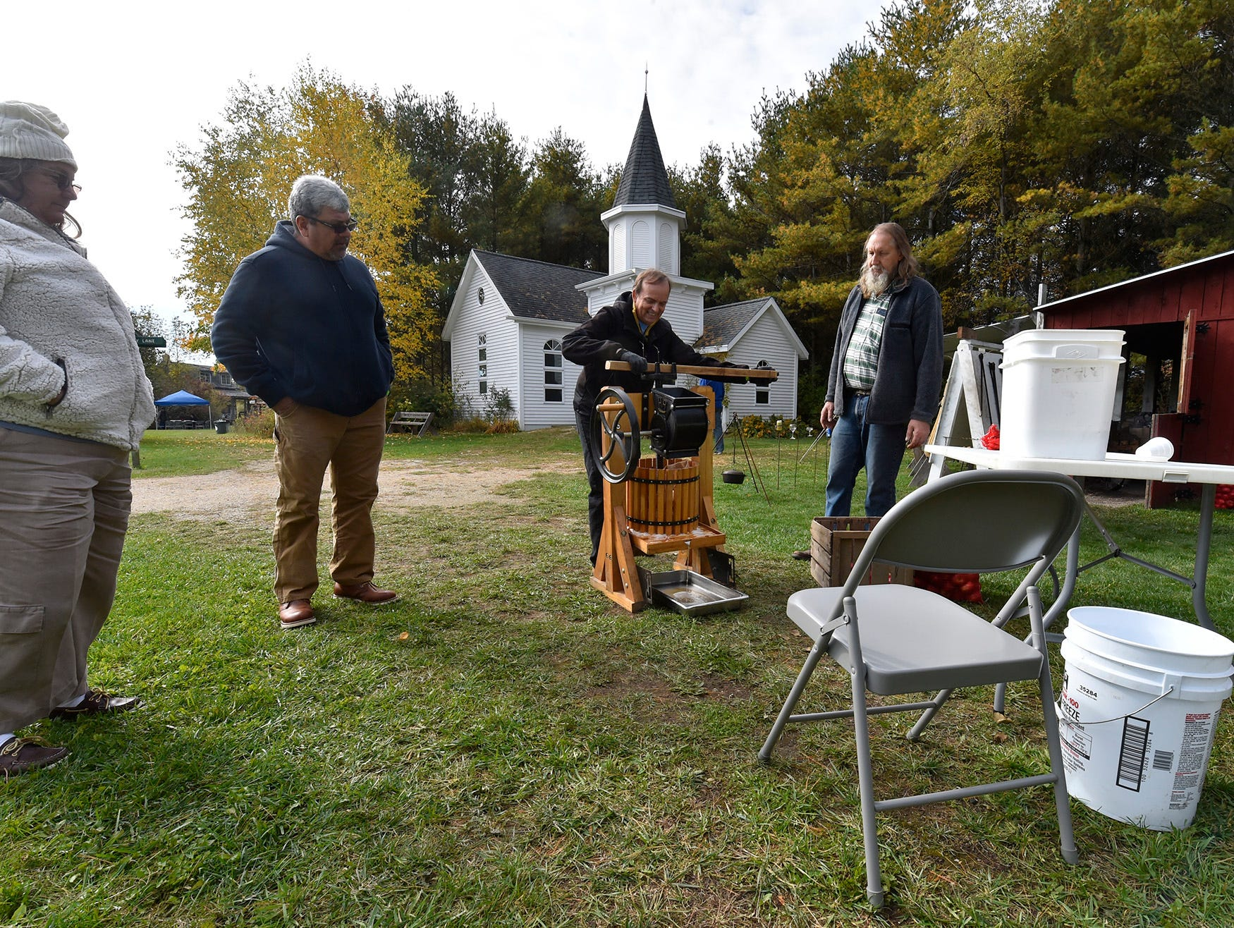 Larry Stuth, right, instructs visitors how to work an apple press to make cider including David Wester of Sturgeon Bay/Miami during Apple Day at Heritage Village at Big Creek in Sturgeon Bay on Oct. 13, 2018. Tina M. Gohr/USA TODAY NETWORK-Wisconsin