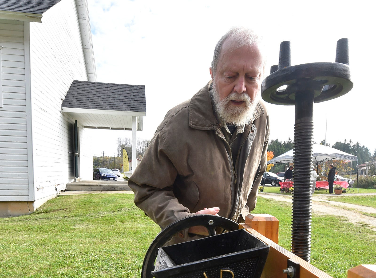 George Zachariasen of Jacksonport learns how to operate an apple press that grinds apples into chunks and pressed into cider during Apple Day at Heritage Village at Big Creek in Sturgeon Bay on Oct. 13, 2018. Tina M. Gohr/USA TODAY NETWORK-Wisconsin