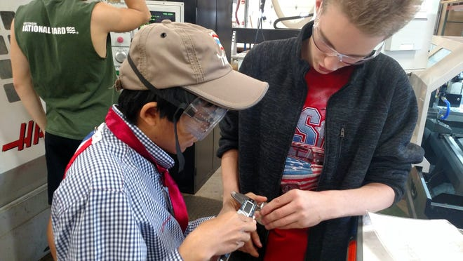 Webster High School Student, Evan Mckee, shows foreign exchange student, Aun Dechsuwan, how to inspect the part per print tolerances