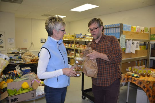 Adam Goettelman, right, owner of Healthy Way Market in Sturgeon Bay, hands a grocery donation to Sandi Soik, manager of the Lakeshore Community Action Program in Sturgeon Bay on Oct. 11, 2018.