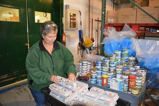 Amy Kinnard, food pantry manager at Lakeshore CAP in Sturgeon Bay, inventories donations.