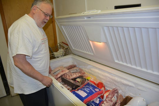 Kerry Isensee of Sturgeon Bay, a volunteer at the Lakeshore Community Action Program food pantry,  shows the contents of one of the frozen meat cases to a client shopping for groceries Oct. 11, 2018.
