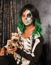 Pacific Daily News reporter Chloe Babauta holds the fake skeleton of a canine while in costume as a half skull thing, Oct. 9, 2018.