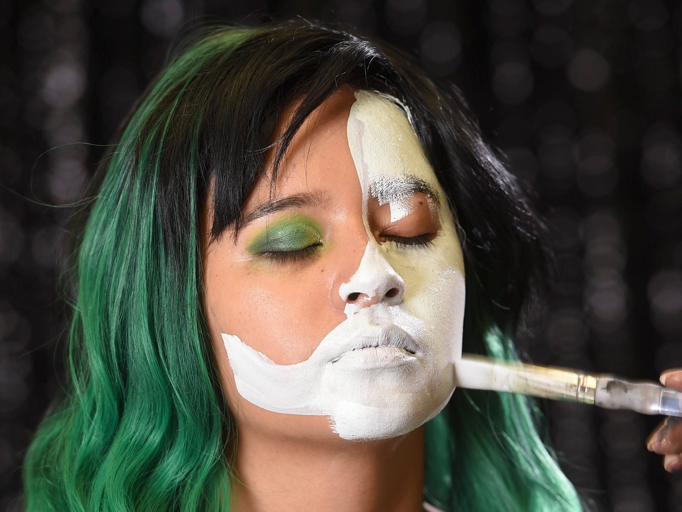 Using white face paint, map out the half skull shape and fill in.