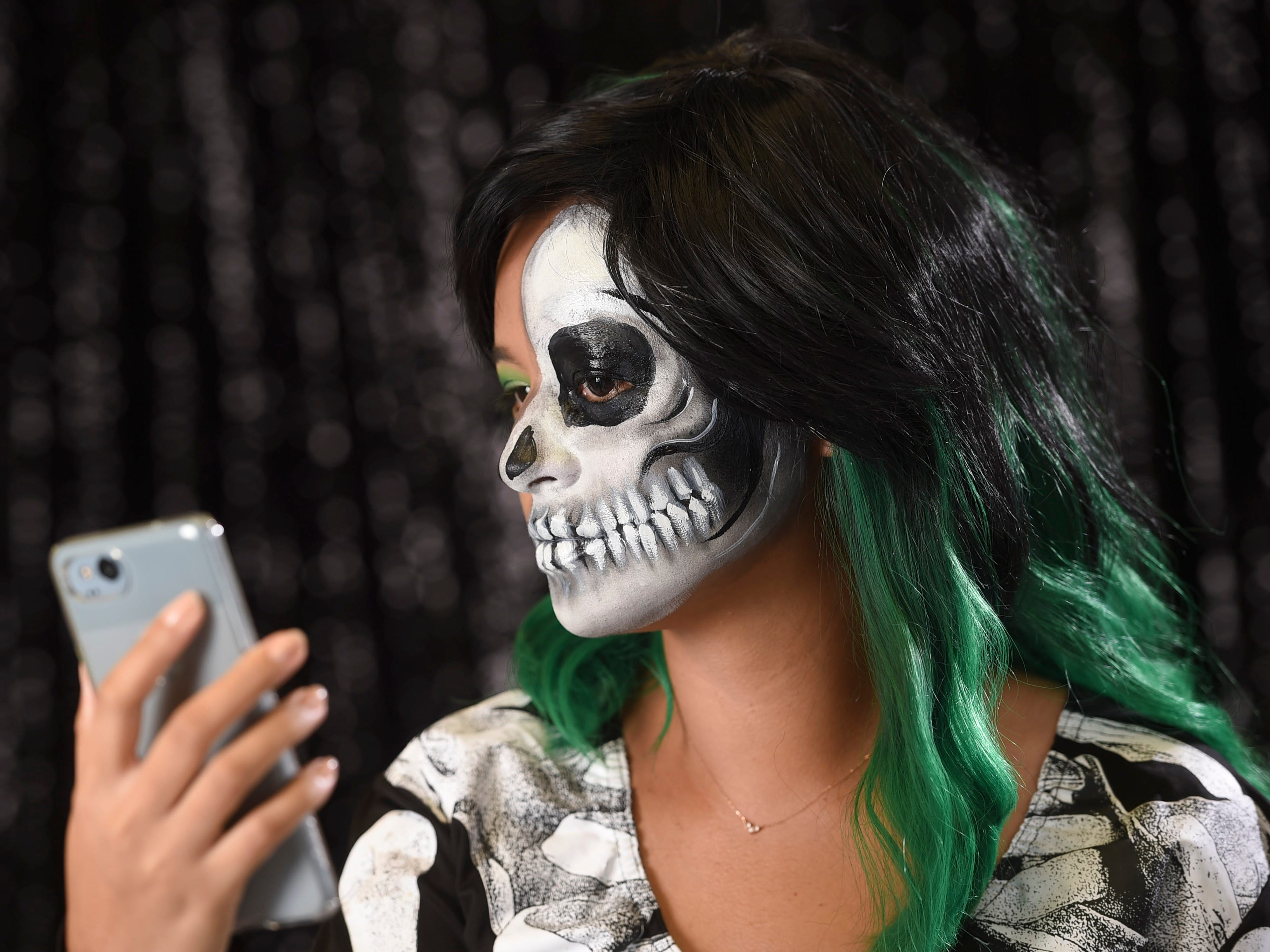 Pacific Daily News reporter Chloe Babauta checks out her half skull makeup, Oct. 9, 2018.