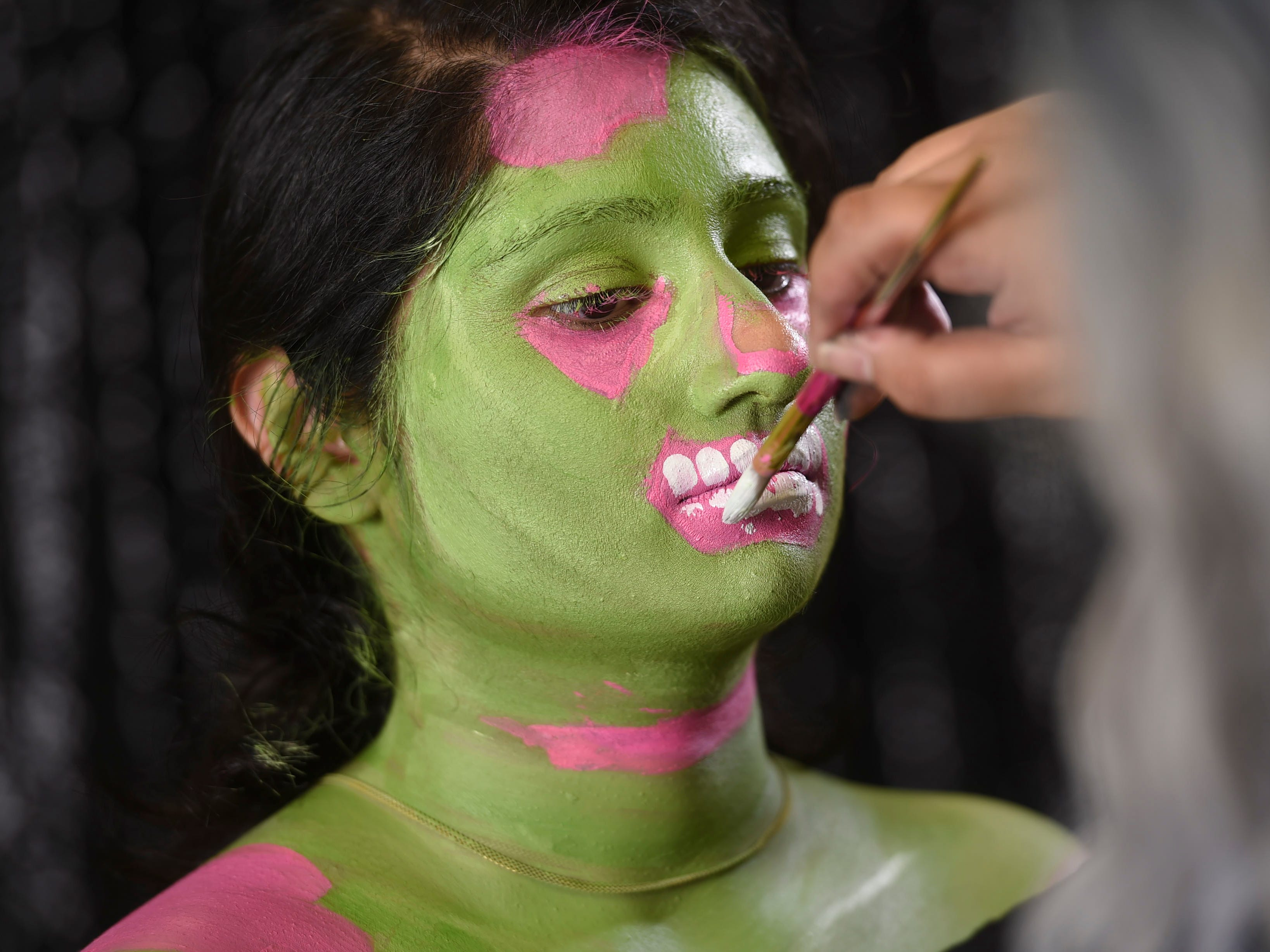 Paint in teeth with white water-based face paint.