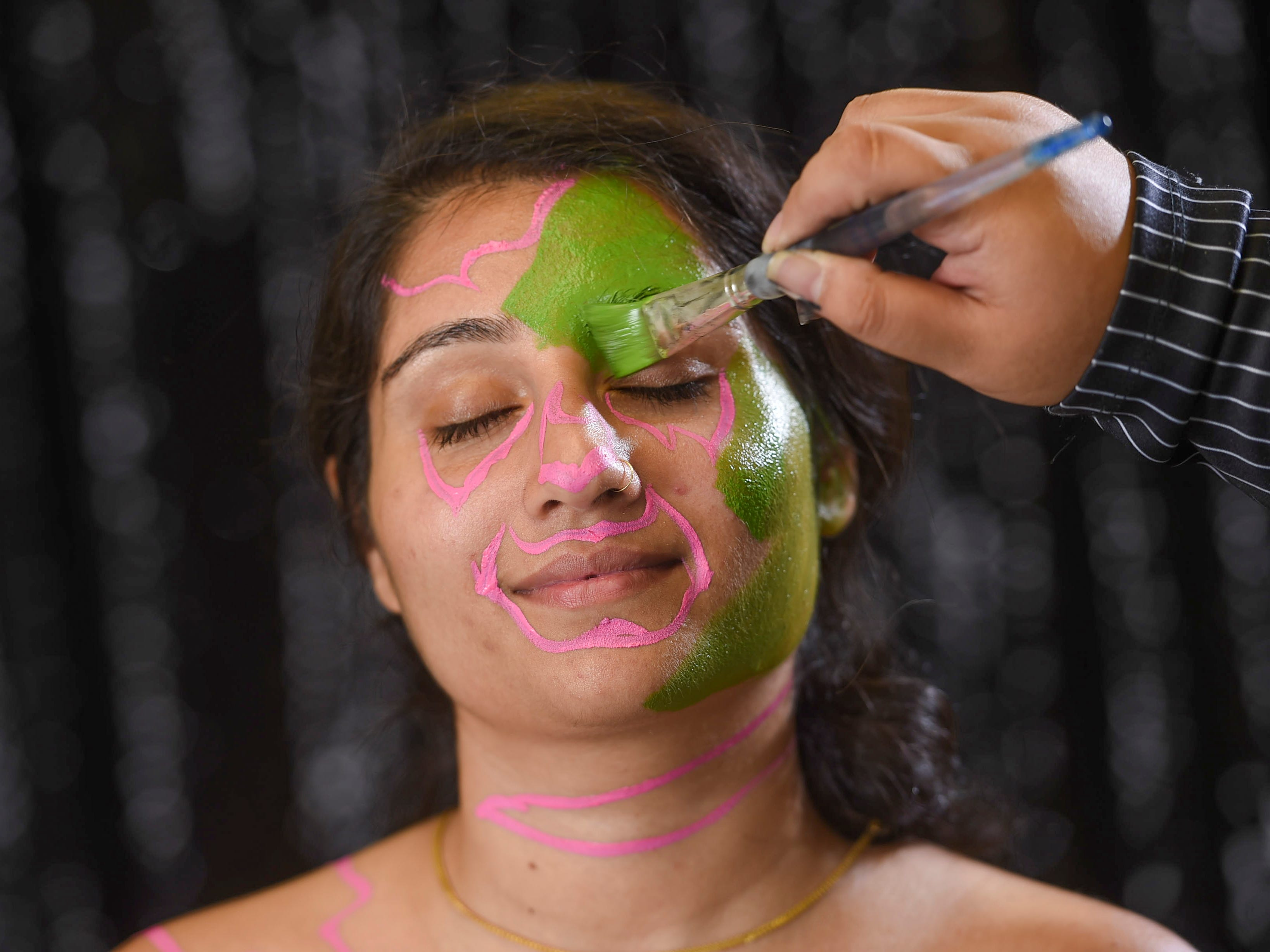 After the pink paint dries, fill in the face and body with green water-based face paint using a thicker paintbrush.