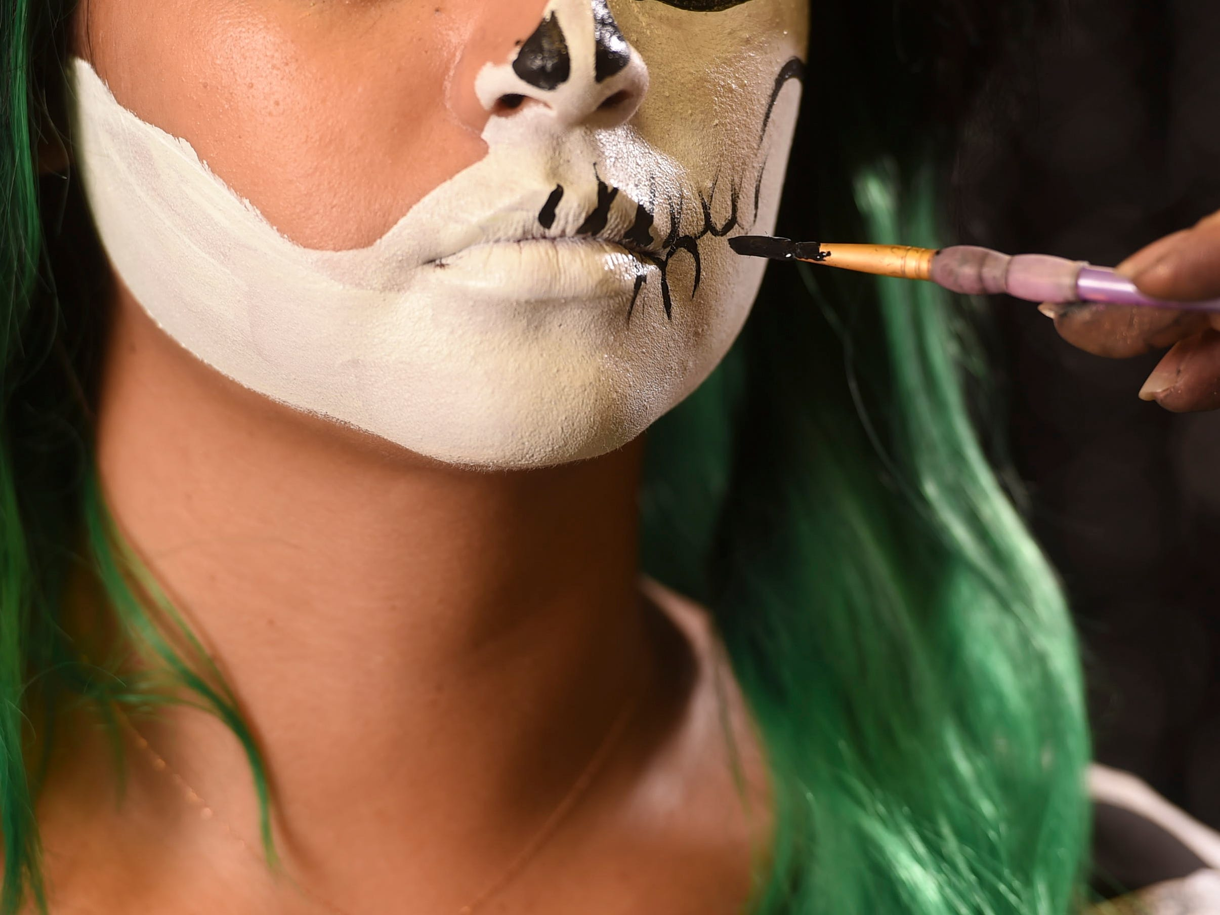 With black face paint, outline your skull eye and teeth.