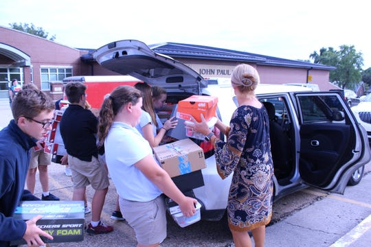 JPII students assist Mr. Drennan in filling his car with the Navajo boxes, every empty space was filled with a box.