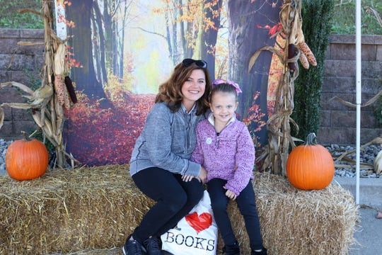 Amber Wolfe and her daughter, Ainsley, take advantage of the fall photo booth.