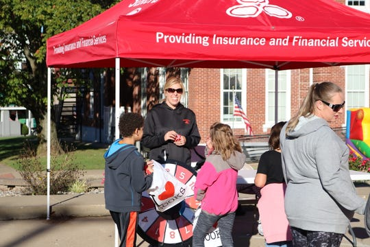 Carrie Divine hands out giveaways at the State Farm booth during the festival.