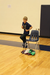 Ethan Byrd runs around a chair during the Minute to Win It Game.