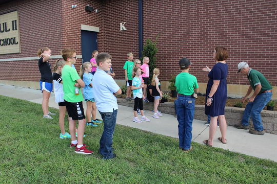 Mrs. Thomas is explaining the process to the group of 4-H members before they begin digging the soil.