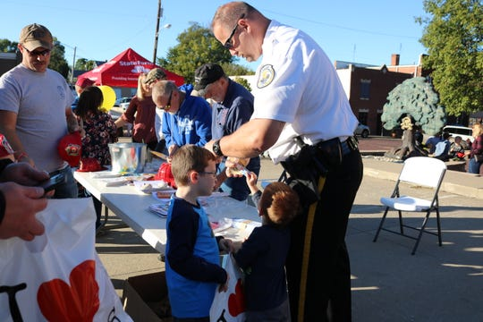 Morganfield Police Chief Geoff Deibler hands out stickers to children at the event.
