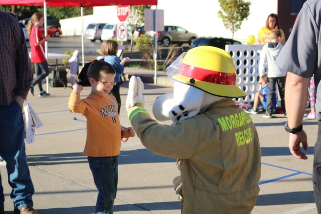 Carl Hazekamp gives a high five to Fire Dog Sparky at the 2018 Fall Family Fun event.