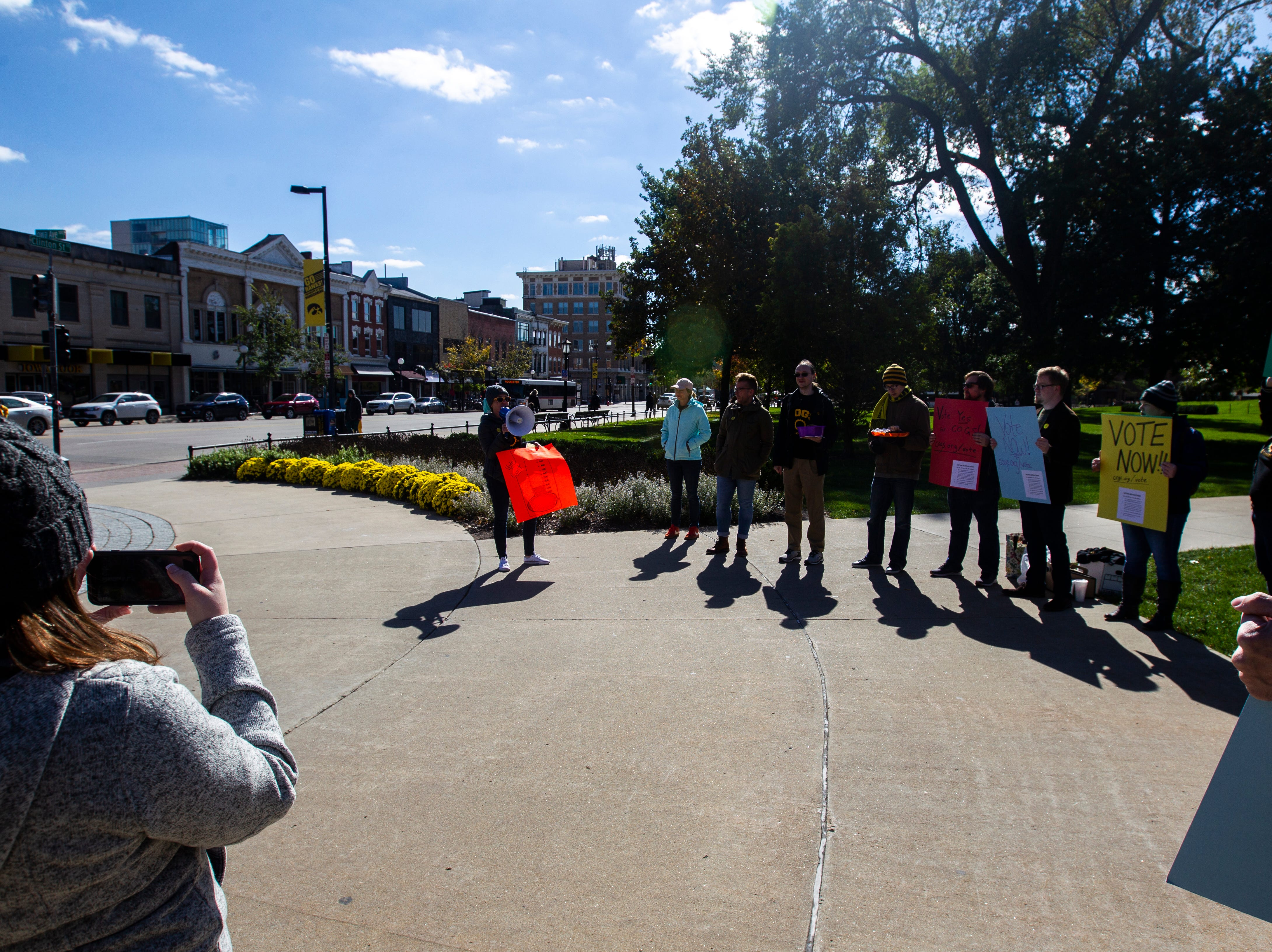 Laura Szech, the Campaign to Organize Graduate Students president, speaks while members hold a demonstration on Monday, Oct. 15, 2018, on the Pentacrest along Clinton Street in Iowa City.