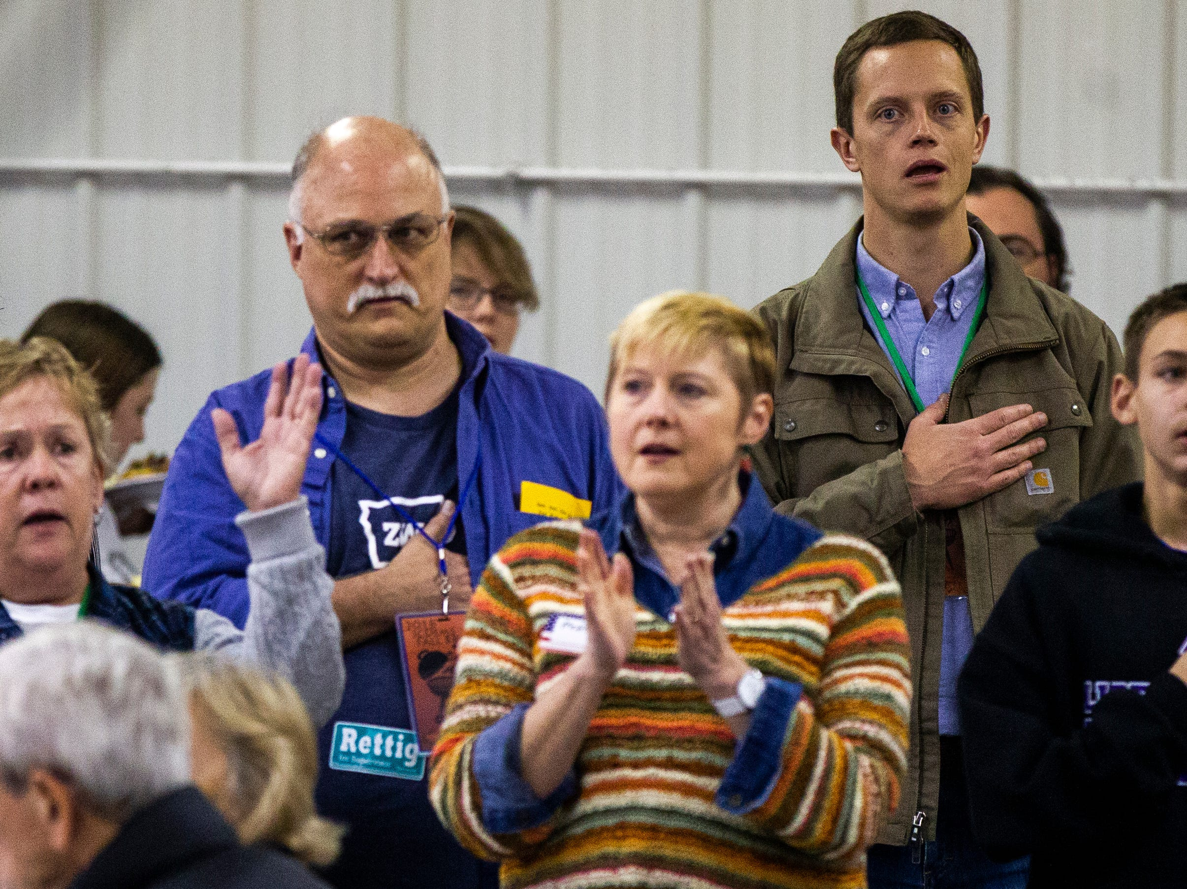 Rob Sand, Democratic candidate for Iowa State auditor, stands during the national anthem during the Johnson County Democrats annual barbecue fundraiser on Sunday, Oct. 14, 2018, inside Building C at the Johnson County Fairgrounds in Iowa City.