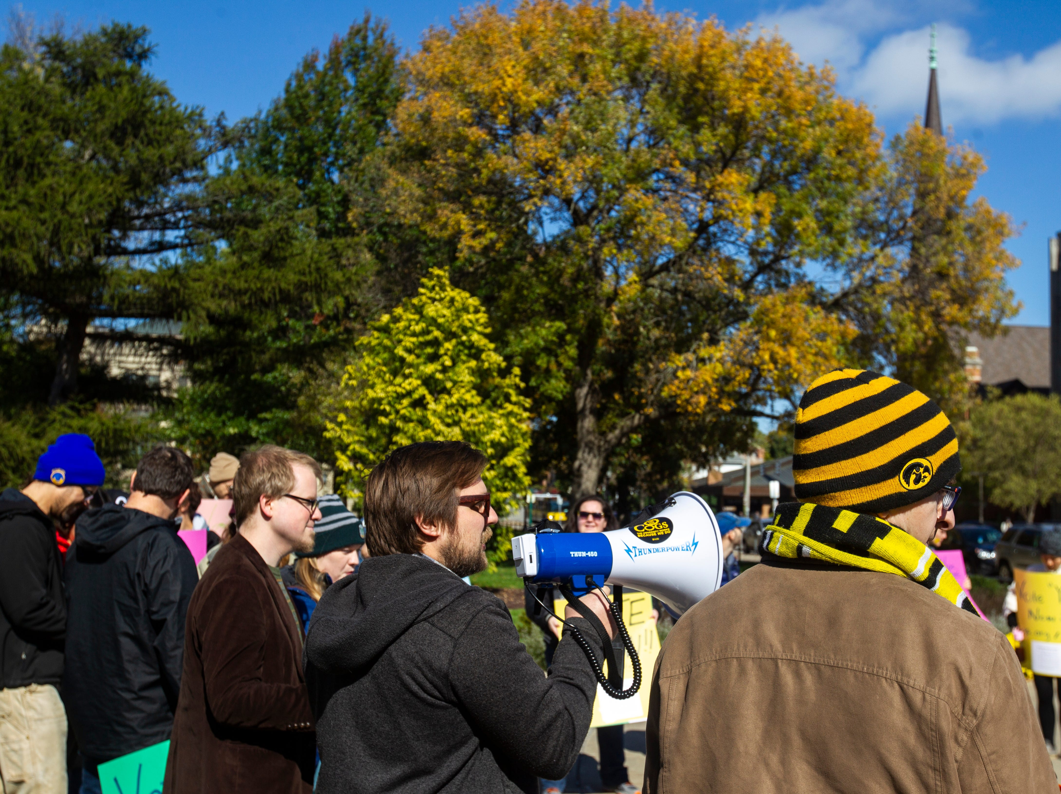 Caleb Klipowicz speaks while Campaign to Organize Graduate Students members hold a demonstration on Monday, Oct. 15, 2018, on the Pentacrest along Clinton Street in Iowa City.
