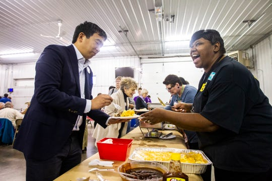 Royceann Porter serves Andrew Yang, 2020 Democratic presidential candidate from Schenectady, New York, some mac and cheese during the Johnson County Democrats annual barbecue fundraiser on Sunday, Oct. 14, 2018, inside Building C at the Johnson County Fairgrounds in Iowa City.