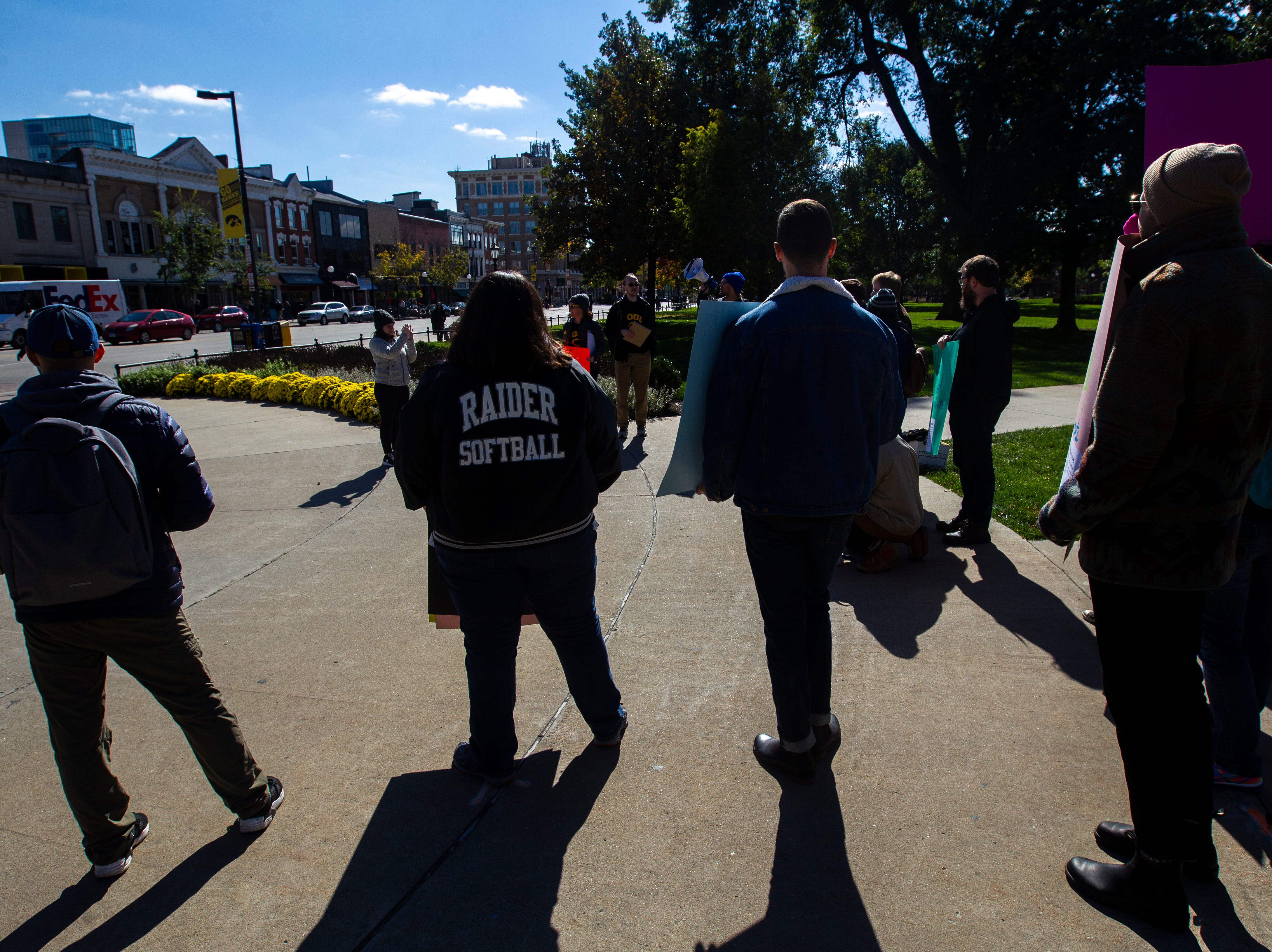 Campaign to Organize Graduate Students members gather while holding a demonstration on Monday, Oct. 15, 2018, on the Pentacrest along Clinton Street in Iowa City.