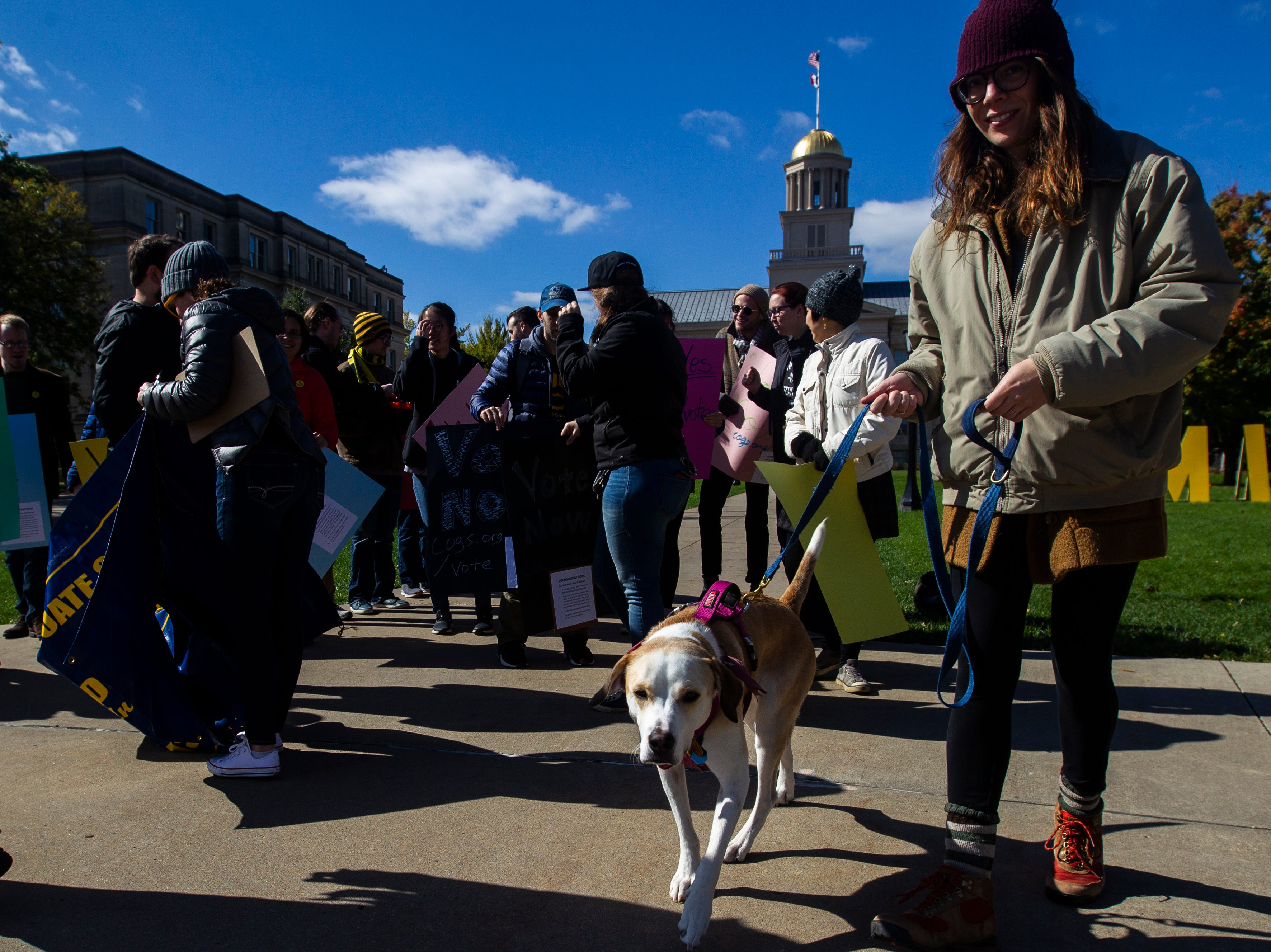 Rachel Jepsen walks with her dog Bird after attending a Campaign to Organize Graduate Students demonstration on Monday, Oct. 15, 2018, on the Pentacrest along Clinton Street in Iowa City.