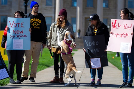 Rachel Jepsen plays with her dog Bird while standing with her husband John, a graduate student in the history department, while Campaign to Organize Graduate Students members hold a demonstration on Monday, Oct. 15, 2018, on the Pentacrest along Clinton Street in Iowa City.