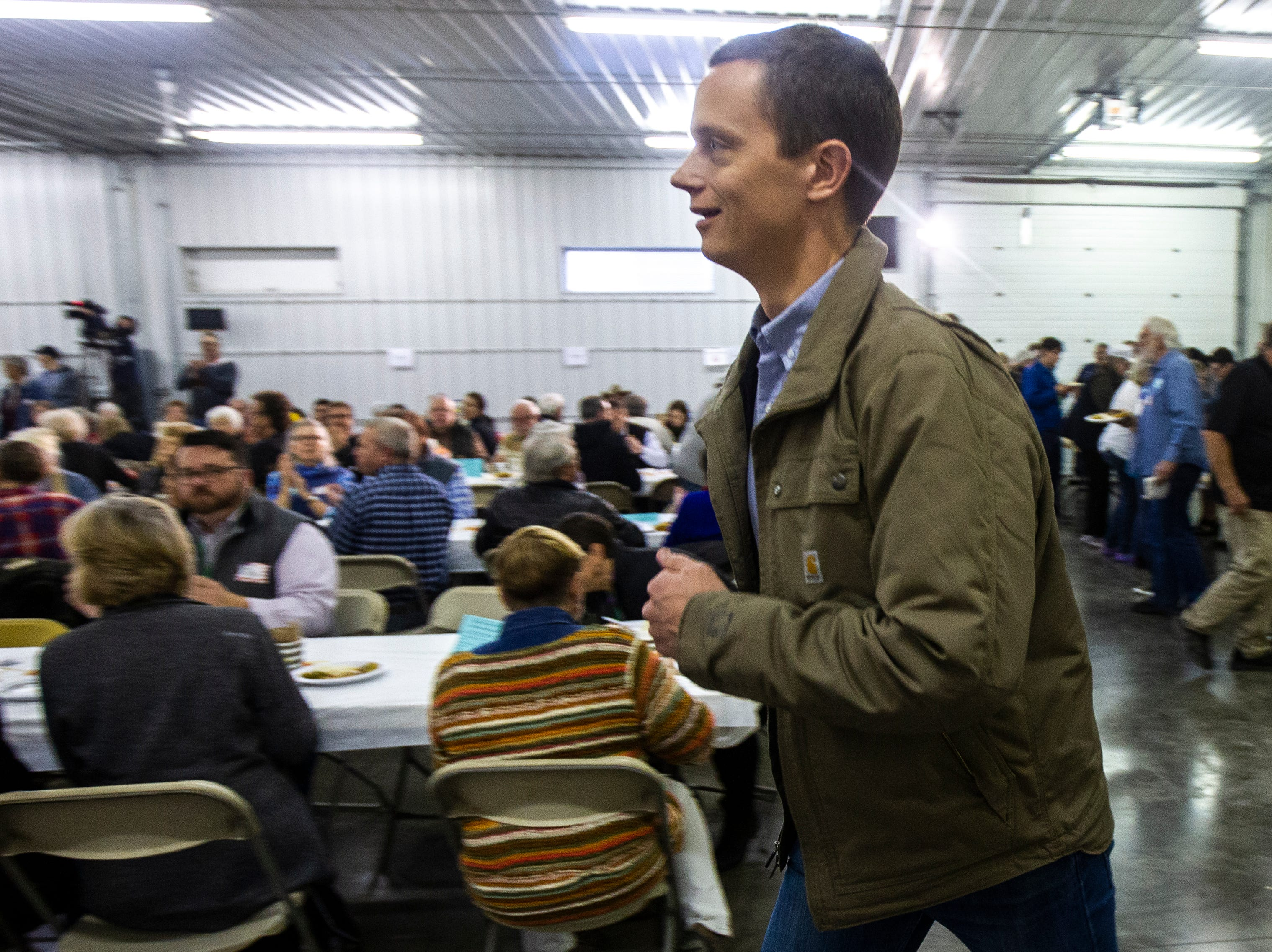 Rob Sand, Democratic candidate for Iowa State auditor, jogs to the stage to speak during the Johnson County Democrats annual barbecue fundraiser on Sunday, Oct. 14, 2018, inside Building C at the Johnson County Fairgrounds in Iowa City.