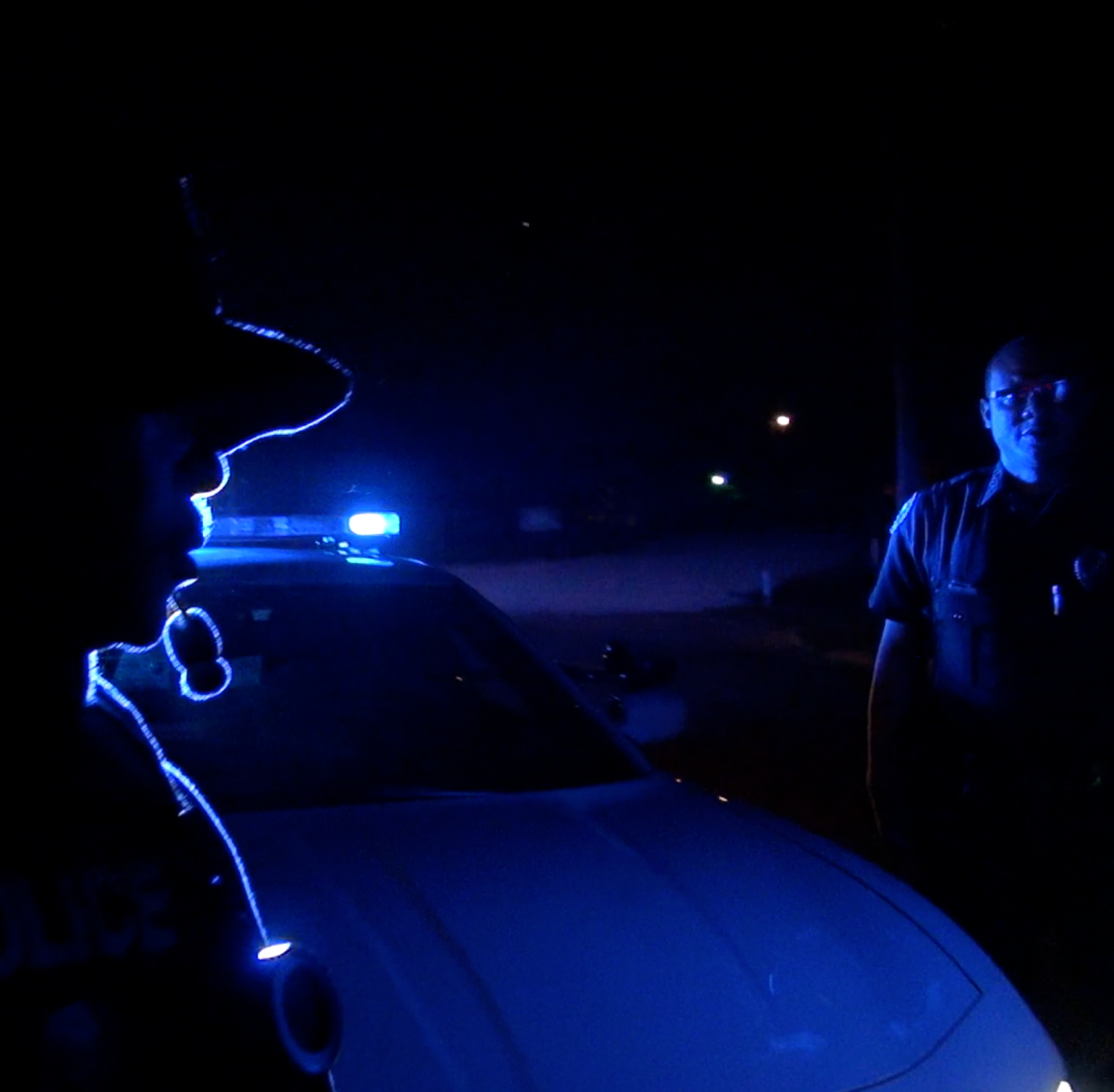 A Jackson police officer is silhouetted by the blue lights.