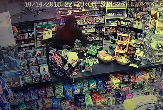 This is a surveillance image of an armed robbery suspect.