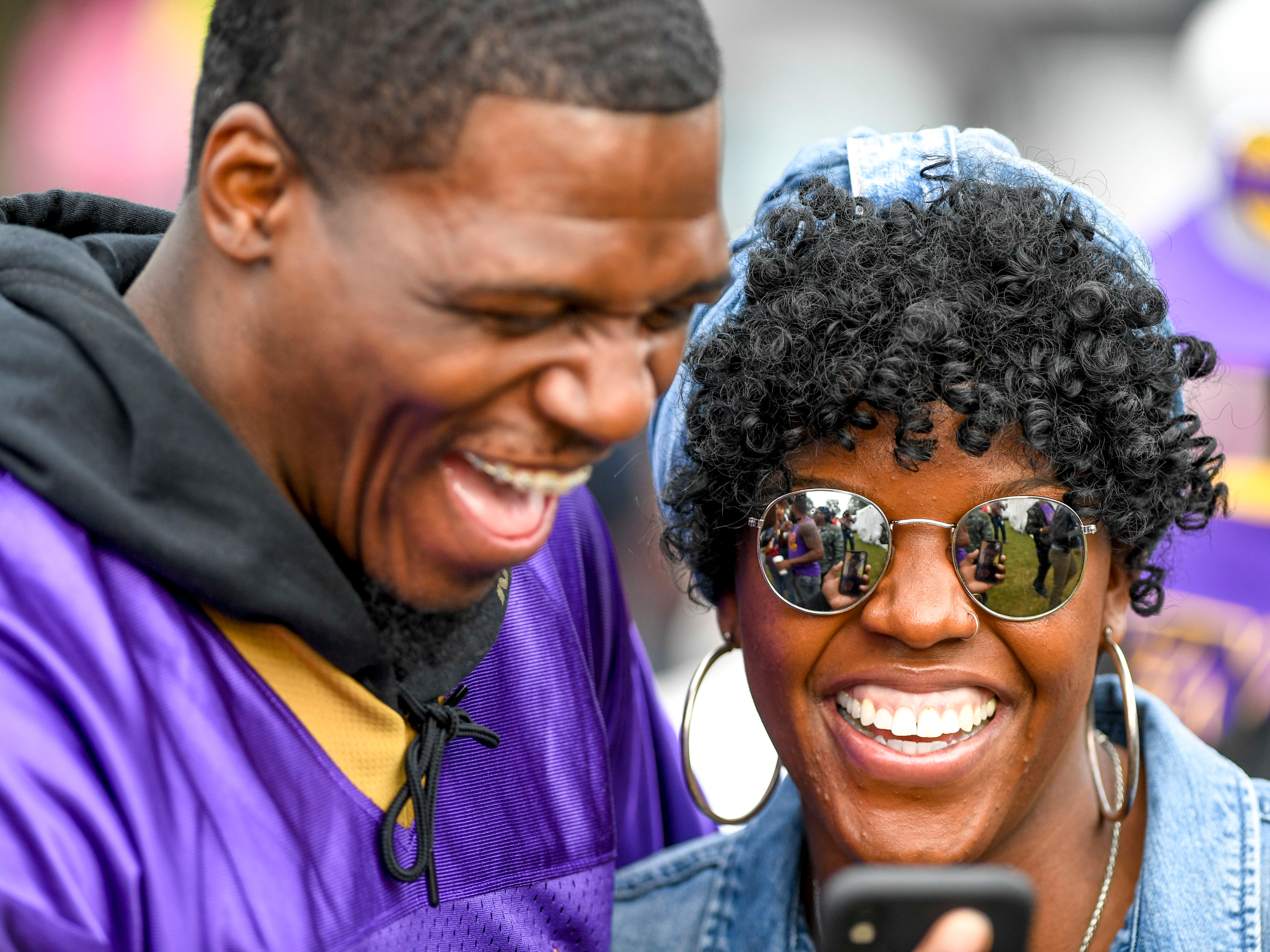 Roderick Thomas, left, and Norca Lou, right, laugh while video chatting with a friend amidst homecoming celebrations at T.R. White Sportsplex in Jackson, Tenn., on Saturday, Oct. 13, 2018.
