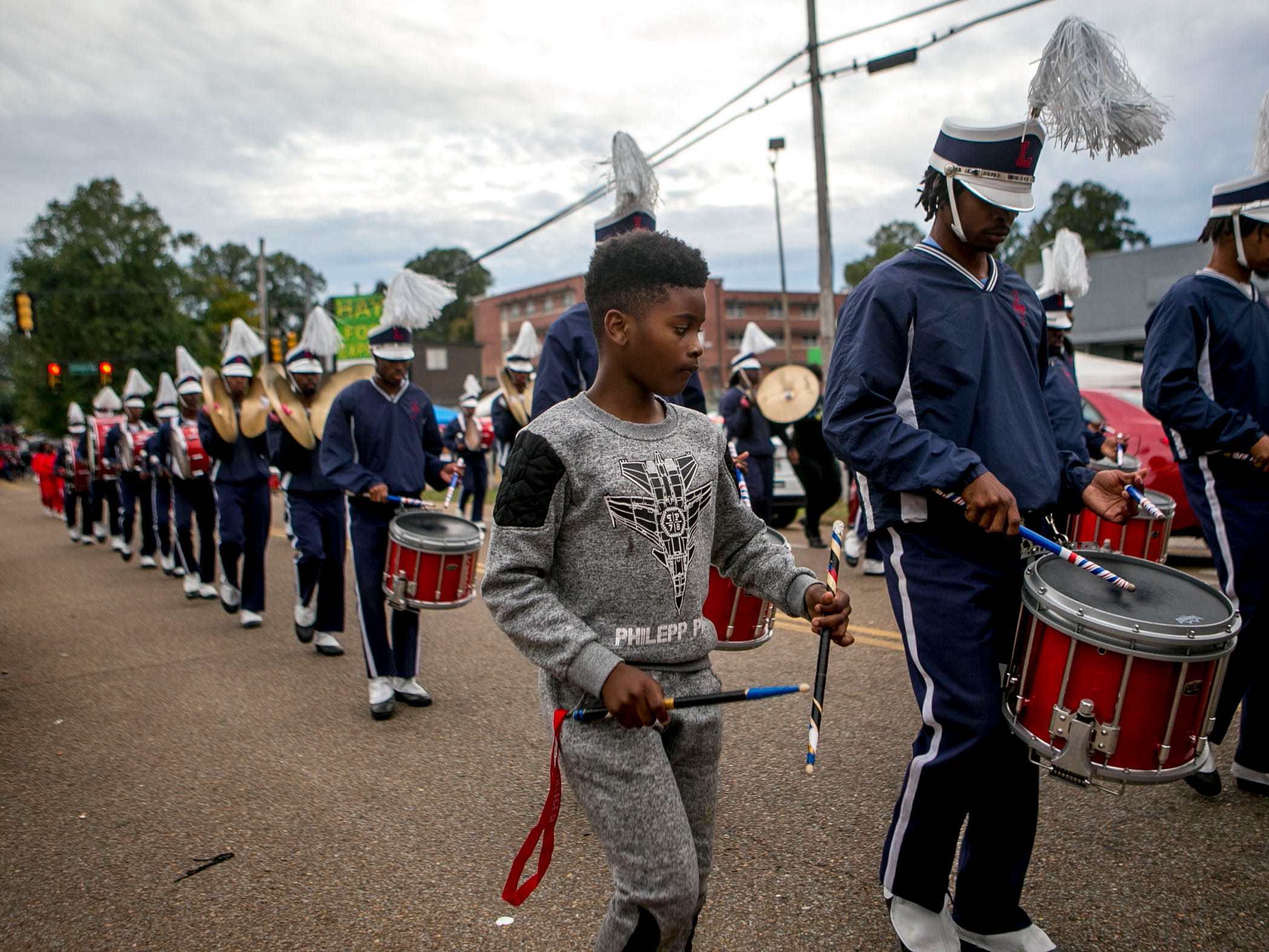 Jaylin Agnew, center, mimics his brother Brandon Agnew's high stepping and snare playing while the Lane College marching band moves back to Lane College at T.R. White Sportsplex in Jackson, Tenn., on Saturday, Oct. 13, 2018.