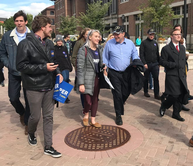 Sen. Joe Donnelly, D-Indiana, walks with Purdue University students and supporters on the way to an early voting site Monday at Purdue's Stewart Center.