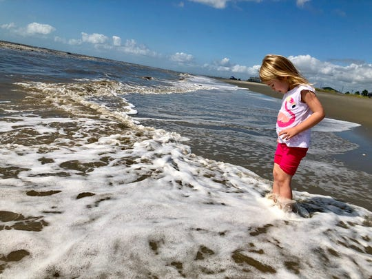 Avery Guidry, 4, dips her toes in the Gulf of Mexico during a day trip to Holly Beach along the Creole Nature Trail American Road that takes visitors through Cameron Parish.