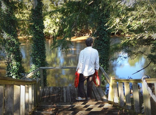 Spaine Edler, who is known for making images that poke fun at south Louisiana, is pictured along the Bayou Teche in New Iberia.