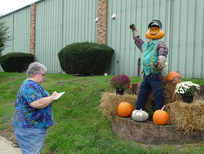 Kathy Young, of New Lexington, judges the Worthington Industries scarecrow as part of the Bremen Area Chamber of Commerce scarecrow contest on Friday, Oct. 12, 2018. Young and Eagle-Gazette reporter Spencer Remoquillo judged 16 scarecrows made by area businesses, residents and groups in what organizers hopes to become an annual tradition.