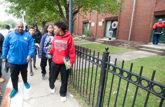 """Kentucky Commissioner of Education Wayne Lewis, left, joins """"Balling for a Cause"""" students in leafleting City View apartments, across the street from the Chestnut Street YMCA where Lewis and the group met earlier."""