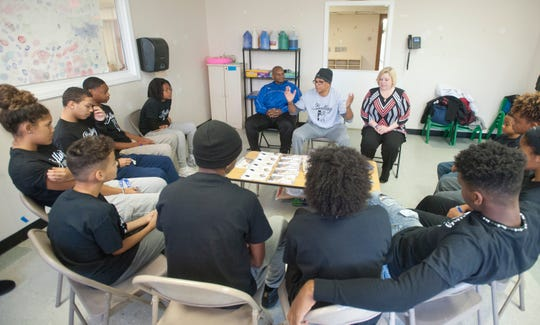 Christopher 2X (center) speaks while Kentucky education chief Wayne Lewis (left, in blue), YMCA official Jenny Benner (right) and Louisville teens listen at a Balling for a Cause meeting.